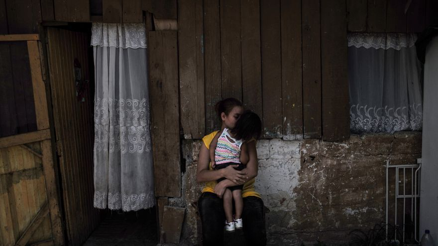 Una mujer y su hija frente a su casa, en el barrio de La Victoria, Honduras, la misma noche en la que asesinaron a cinco personas | FOTO: Unicef