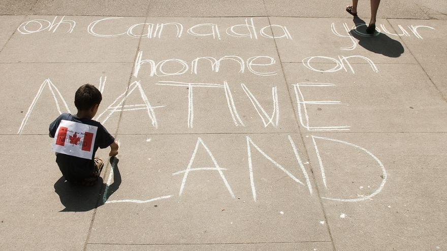 Un niño escribe en el suelo durante una protesta por los derechos de los pueblos originarios en Canadá.