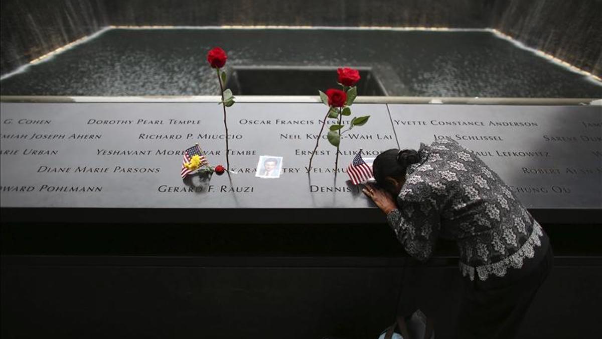 Una mujer se inclina sobre los nombres de las víctimas del 11-S en la fuente conmemorativa en Nueva York.