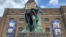 09 June 2020, England, London: The statue of Robert Milligan, a noted West Indian merchant, slaveholder and founder of London's global trade hub, West India Docks, is covered in a cloth and Black Lives Matter sign outside the Museum of London Docklands. Photo: Renee Bailey/PA Wire/dpa