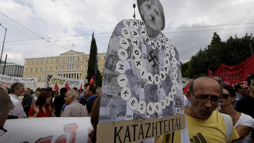 "A protestor holds a banner with the picture of the German Chancellor Angela Merkel ( with a nazi moustache ) that reads ""wanted"" and ""war compensations"" during a protest in Athens on Tuesday Oct. 9, 2012."