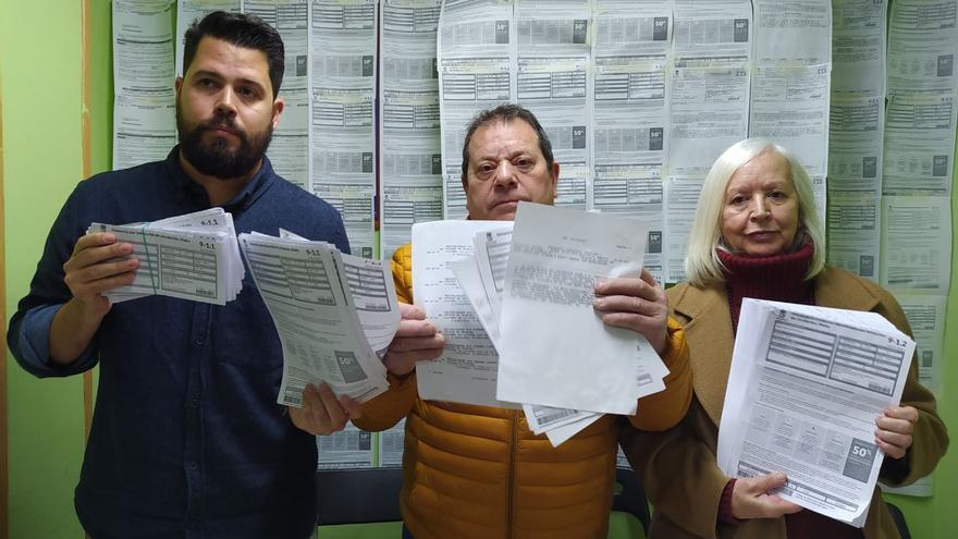 Carlos, Ángel y Ángela, tres vecinos de Lavapiés y Las Letras afectados. Detrás, la pared empapelada de multas. / SPM