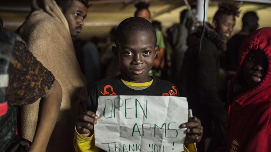 Uno de los menores rescatados enseña un cartel en agradecimiento al Open Arms.