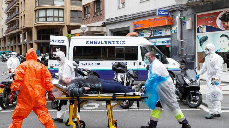 Efectivos del Cuerpo Municipal de Bomberos de San Sebastián ayudan a trabajadores del Servicio Vasco de Salud Osakidetza a trasladar a una persona enferma y con dificultades de movilidad.