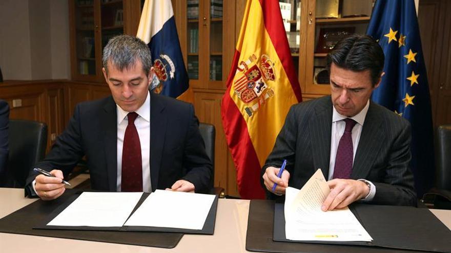 El presidente del Gobierno de Canarias, Fernando Clavijo (i), y el ministro de Industria, Energía y Turismo, José Manuel Soria (d), firman el acuerdo entre las dos administraciones sobre el nuevo reglamento de instalación y explotación de parques eólicos en el archipiélago.
