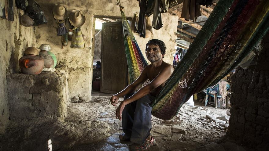 El hermano de Víctor, que ha vivido siempre en casa de su madre, se balancea en una hamaca en el porche de su casa