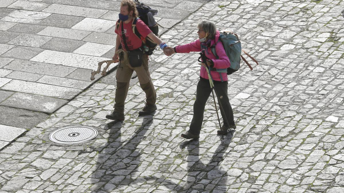 Dos peregrinos en la plaza del Obradoiro esta mañana en Santiago de Compostela. EFE/ Lavandeira Jr