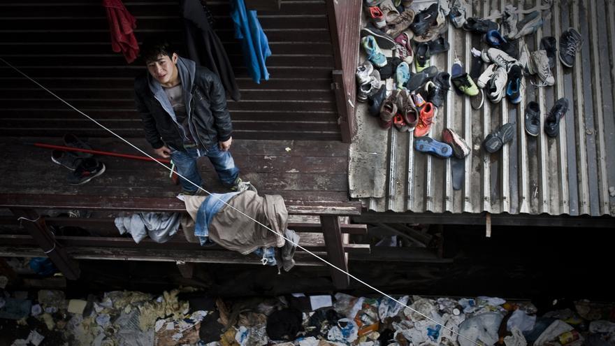 Un joven afgano en una fábrica abandonada de Patras. En el tejado, la basura y los zapatos de decenas de inmigrantes que pasaron por ese recinto/ Fotografía: Aitor Sáez