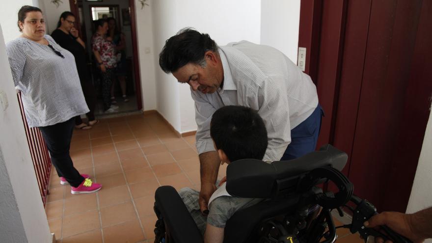 Francisco es ayudado por su padre para poder acceder a su casa.