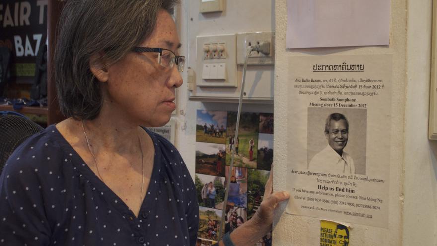 Shui-Meng contempla un cartel en el que se solicita ayuda para encontrar a su marido, el líder comunitario Sombath Somphone, en Vientiane (Laos). | Foto: Carlos Hernández.