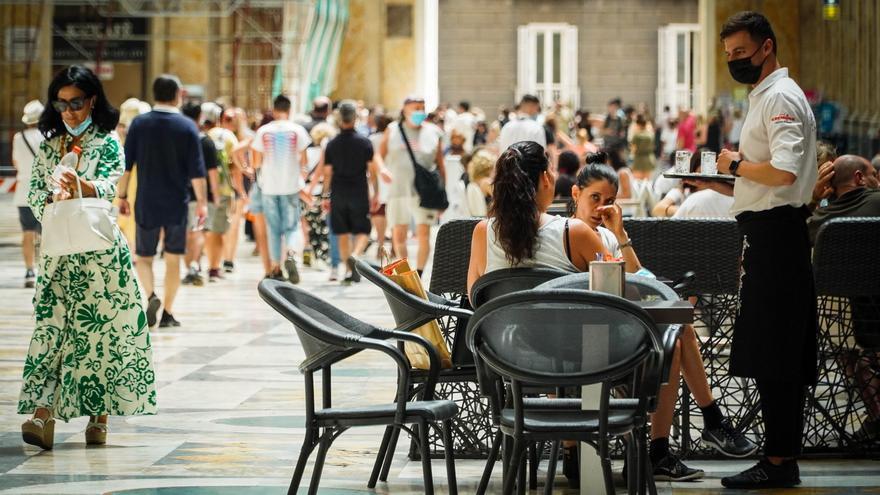 Un camarero atiende a los clientes en la terraza de un restaurante en Nápoles.