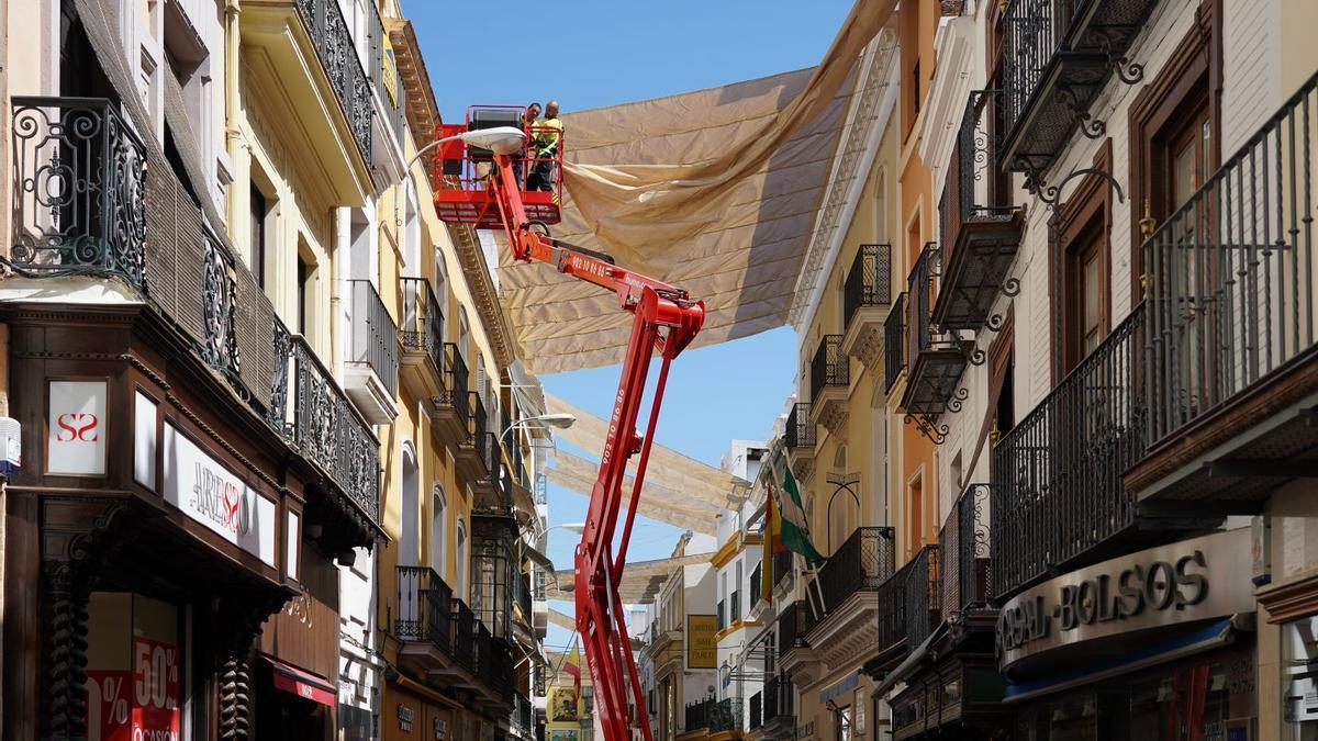 Operarios colocan los toldos en las calles del centro de Sevilla.