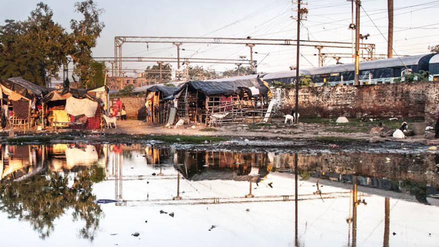 El slum de la estación de Varanasi, con las vías del tren a la derecha. El agua encharcada es fuente de infecciones y provoca la aparición de mosquitos, que transmiten enfermedades mortíferas de animales a personas vulnerables como los niños.