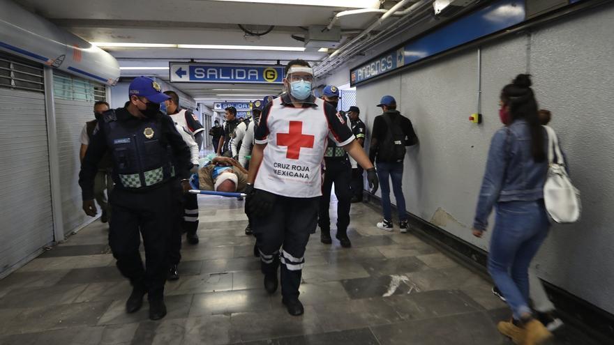 Los paramédicos de la Cruz Roja Mexicana Ernesto Sánchez (d) y Héctor Velázquez (i, atrás) laboran en un llamado de emergencia en el Sistema de Trasporte Colectivo Metro, el 30 de junio de 2020 en Ciudad de México (México).
