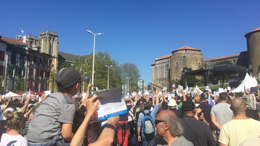 Participantes en la concentración de Bayona levantan las octavillas azules de los artesanos de la paz.
