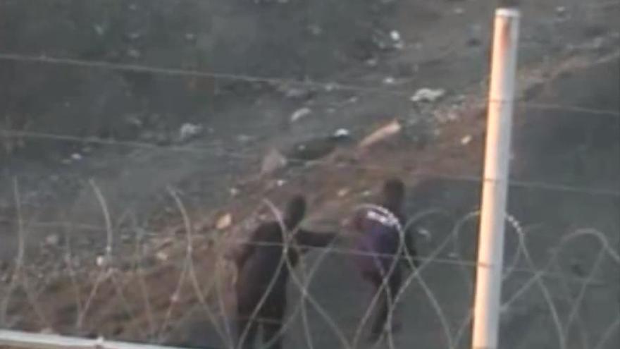 El Guardia Civil, ya en territorio marroquí, empuja a uno de los inmigrantes que consiguió llegar a España.