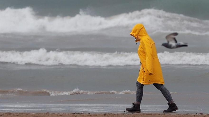 Una persona pasea por la playa de la Malvarrosa bien protegida contra la lluvia.
