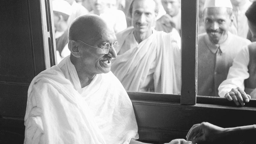 Mahatma Gandhi recibe una limosna en el interior de un tren en 1940.