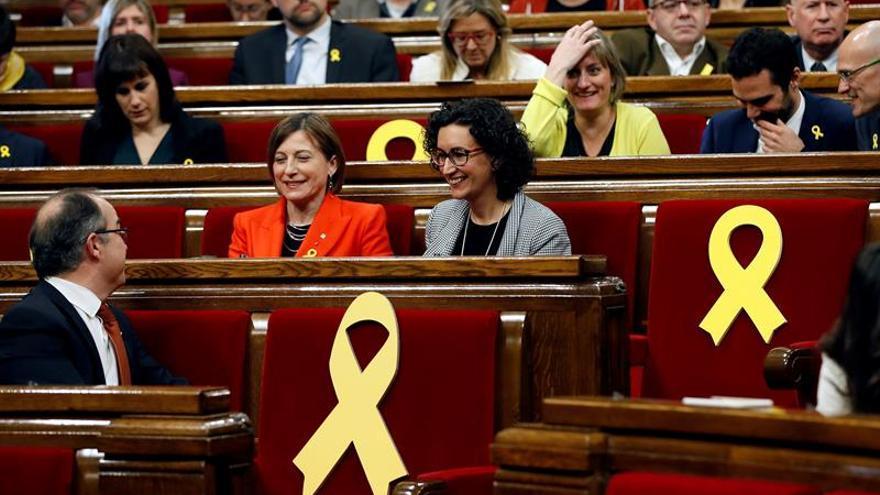 La expresidenta del Parlament, Carmen Forcadell, y la secretaria general de ERC, Marta Rovira, rodeadas por varios escaños vacíos adornados con lazos amarillos / EFE