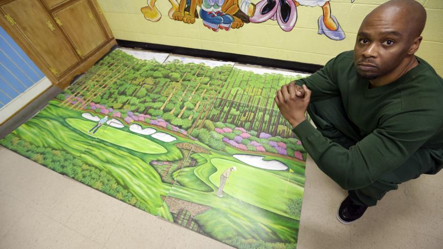 Valentino Dixon posa en la cárcel de Attica junto a uno de sus dibujos en mayo 2013.