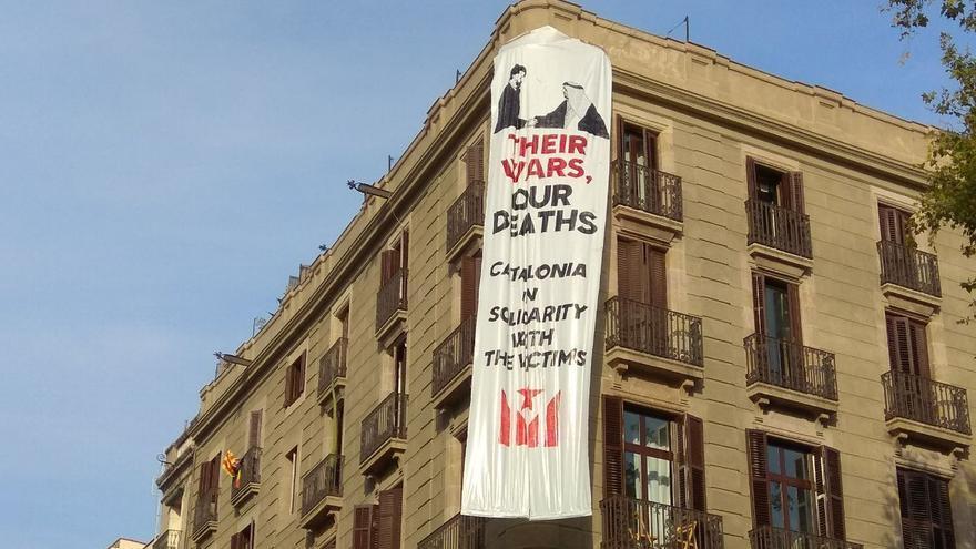 """Cuelgan una pancarta contra Felipe VI con el lema """"sus guerras, nuestros muertos"""" en la Rambla."""