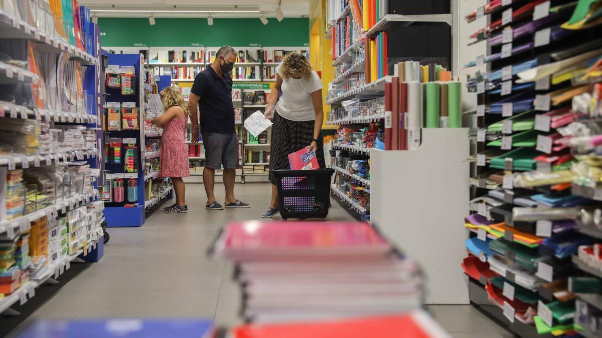 Una pareja acompañados por una niña realizan una compra de material escolar en una papelería