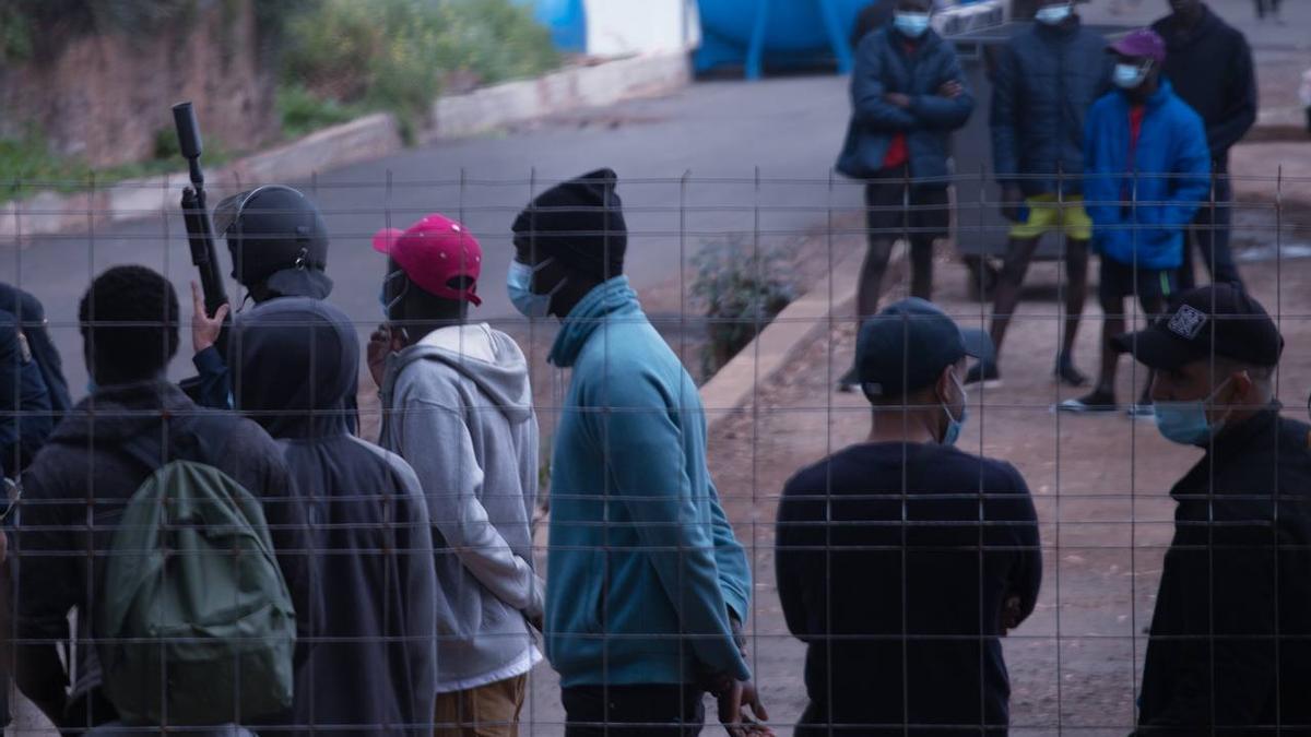 Varios migrantes observan la intervención policial de este martes en el campamento para migrantes de Las Raíces, en Tenerife