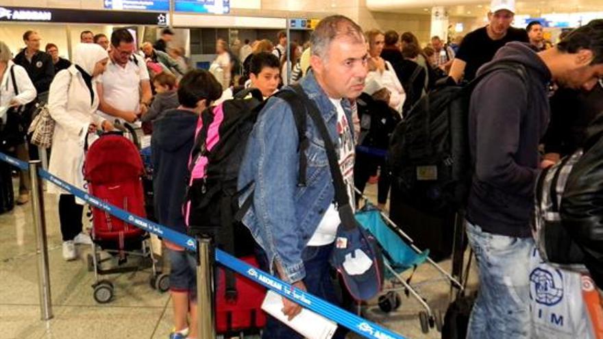 Los refugiados esperan en el mostrador de facturación del aeropuerto de Atenas, antes de partir hacia Madrid.   Foto: EFE