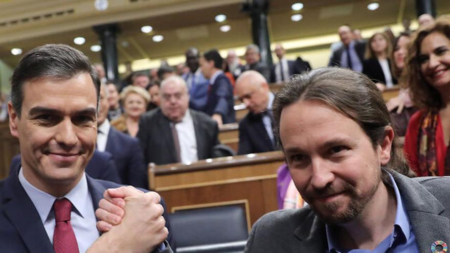 Pedro Sánchez y Pablo Iglesias se estrechan la mano tras la investidura del líder del PSOE.