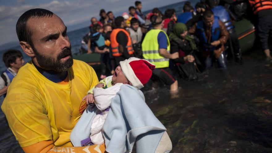 Un voluntario con un bebé en brazos que acaba de llegar a la costa de Lesbos en octubre de 2015. / Socrates Baltagiannis/picture-alliance/dpa/AP Images