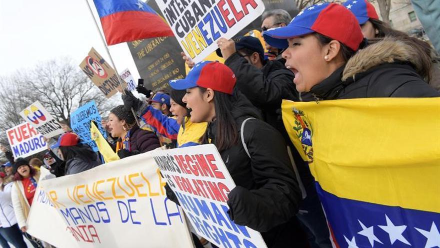 Varias personas sostienen pancartas y banderas venezolanas durante una manifestación de venezolanos convocada por el colectivo Voluntad Popular en la plaza Simón Bolívar, en Washington (EE.UU.)