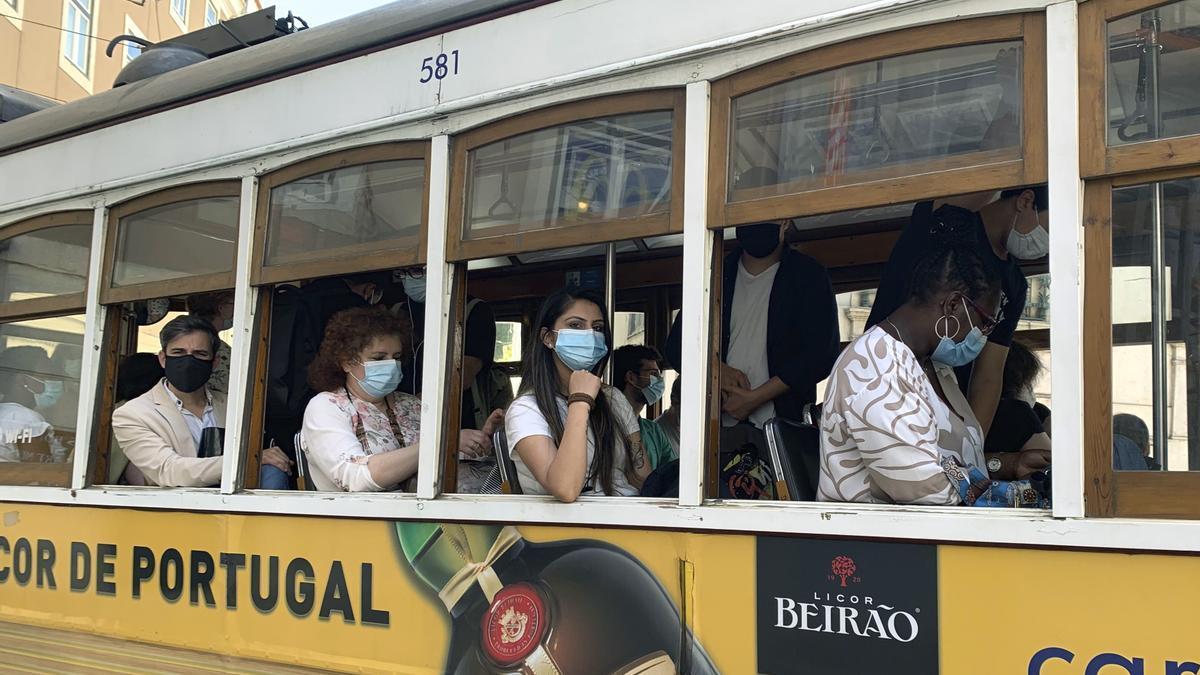 Un grupo de pasajeros con mascarilla en un tranvía por la zona de la Baixa en Lisboa