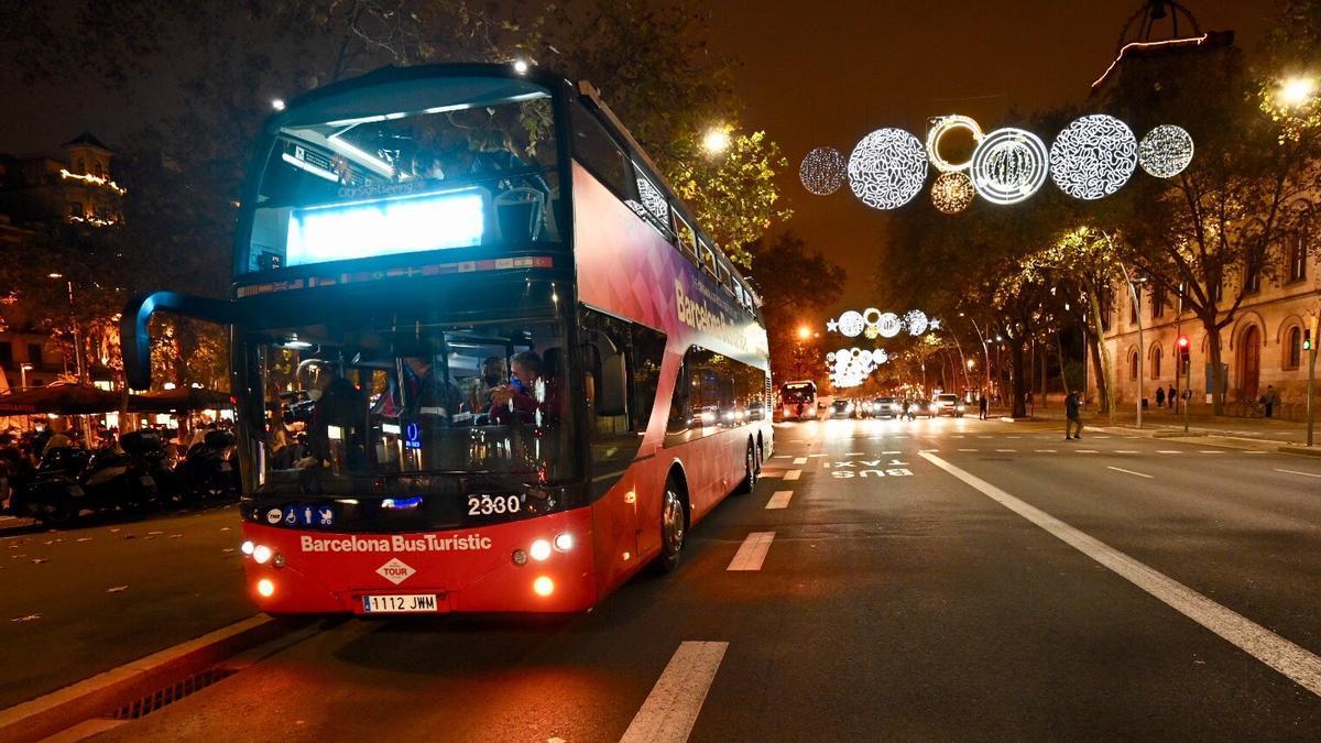 Un autobús turístico de Barcelona circula bajo unas luces navideñas