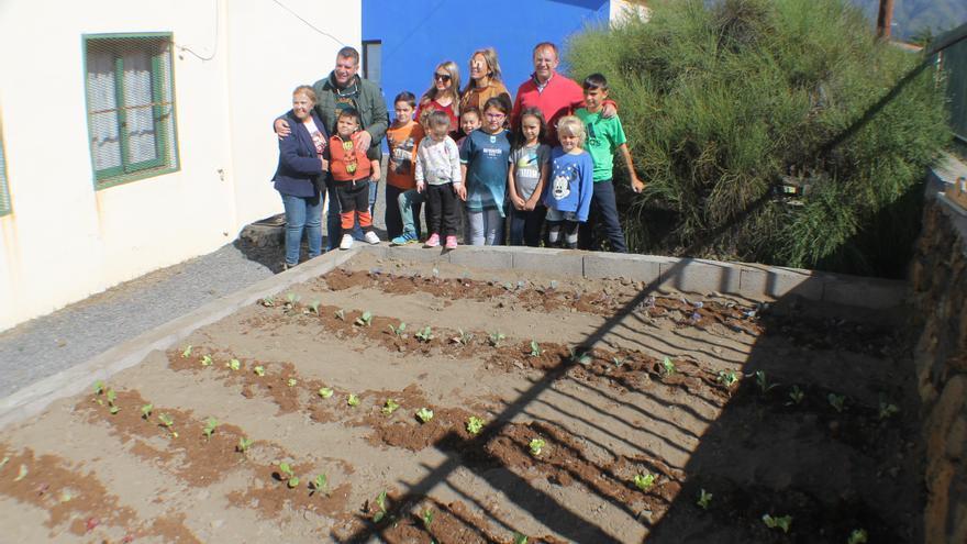 Los responsables municipales con los escolares en un huerto.