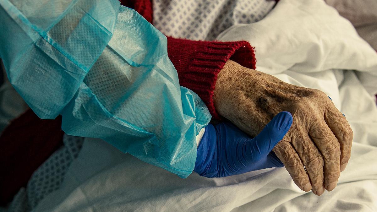 Un sanitario sujeta la mano de una paciente de coronavirus
