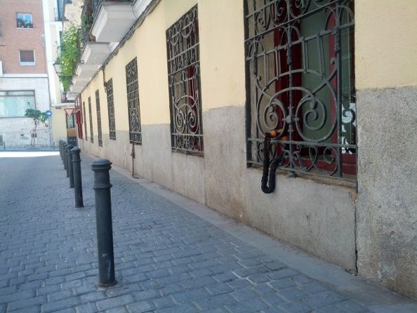 Imagen de la Galería de Robles con cadenas ancladas a unas ventanas donde se aparcan bicicletas   Foto: Somos Malasaña