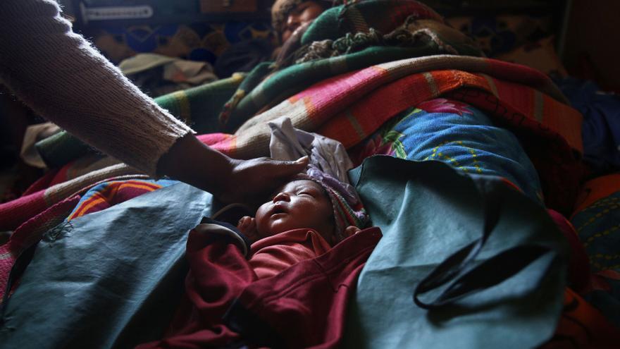Elsa Quispe tumbada junto a su bebé de un día de edad en su casa en Patacamaya, mientras la auxiliar de enfermería Luz Maída lo tapa después de haberlo medido / Fotografía: Olmo Calvo