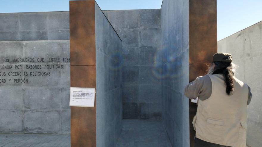 Antolín Pulido, el hombre que convocó como particular el acto, pega con celo un carton que reemplaza una de las placas eliminadas del memorial.