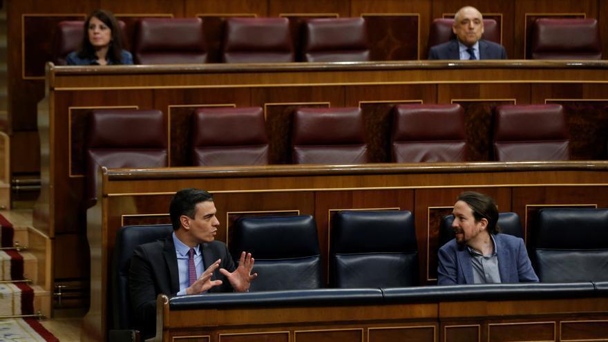 El presidente del Gobierno, Pedro Sánchez (i), conversa con el vicepresidente segundo, Pablo Iglesias, este miércoles, durante una sesión de control al Gobierno en el Congreso de los Diputados