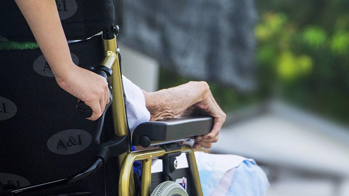 Una cuidadora con un anciano en una silla de ruedas.