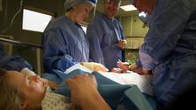 Una mujer observa cómo le sacan su bebé por cesárea