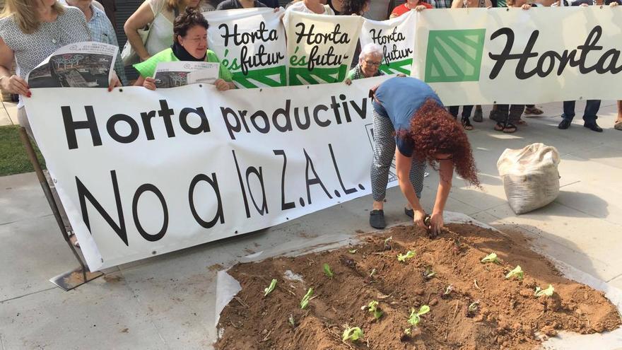 Una de las participantes en la protesta plantando un simbólico huerto