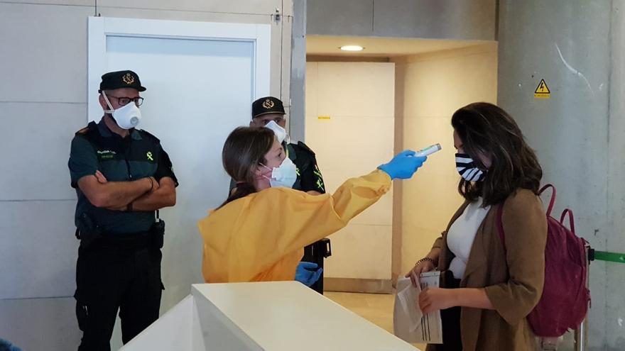 Personal del aeropuerto de Manises toma la temperatura a uno de los pasajeros que han llegado a València este jueves.