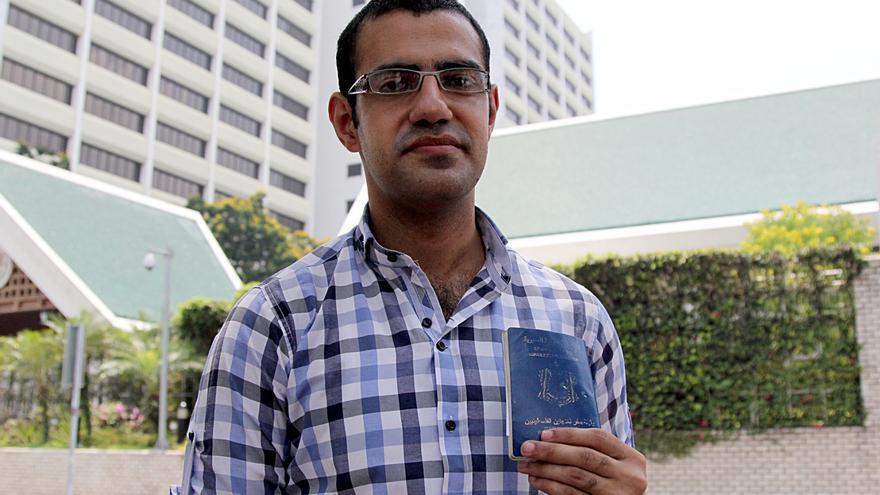 Ibrahim Ghazal posa frente a la sede de Naciones Unidas en Bangkok frente al único documento que tiene, un permiso de viaje que le permitió entrar en Tailandia./ L. Villadiego