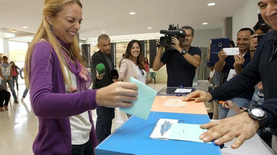 La cabeza de lista de Podemos al Parlamento de Canarias, Noemí Santana, deposita los sobres con su voto en el colegio electoral de Las Palmas de Gran Canaria donde hoy ejerció su derecho al voto. EFE/Elvira Urquijo A.