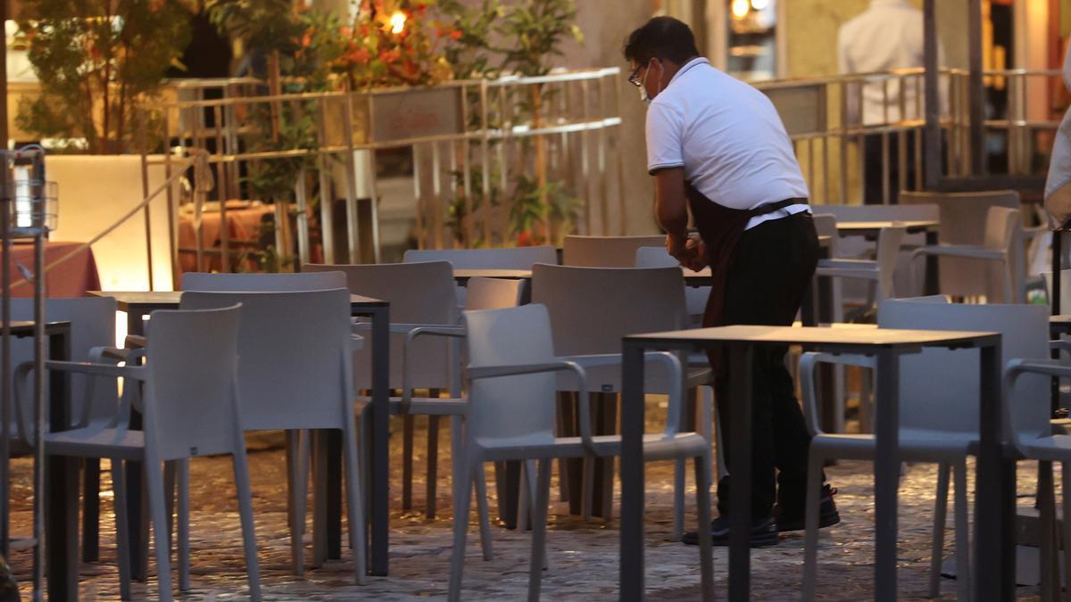 Un camarero prepara una terraza, en una fotografía de archivo. La hostelería es un sector con largas jornadas laborales. EFE/JuanJo Martín