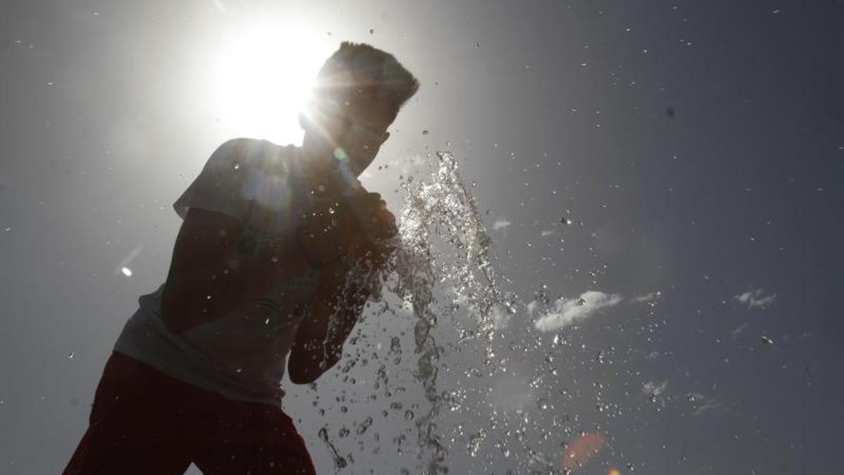 Un joven se refresca con agua