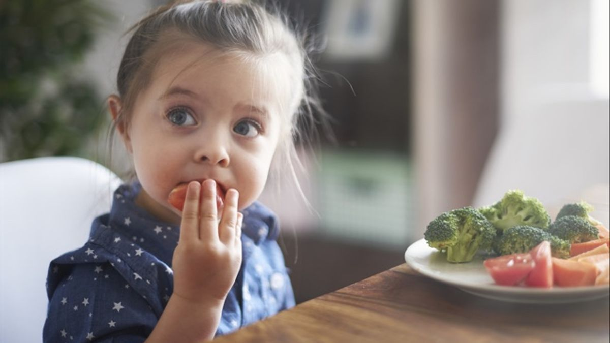 Niña comiendo verdura