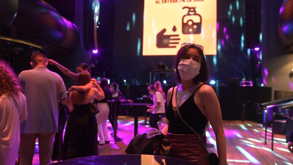 Una joven en una discoteca con advertencias de seguridad relacionadas con el coronavirus.