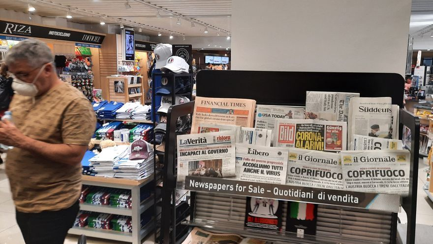 Un hombre con mascarilla camina ante las portadas sobre el coronavirus en Italia, que protagonizan prensa nacional e internacional.